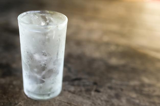 Eau froide en verre sur une table en bois.