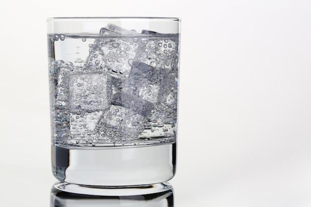Eau gazeuse avec des bulles de glace dans un verre