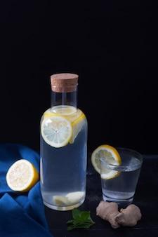 L'eau de gingembre dans une bouteille en verre avec du citron et du miel sur une table noire