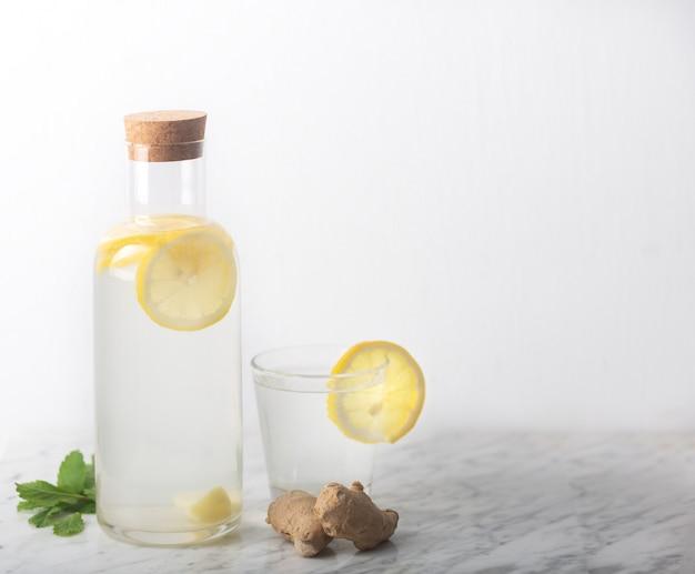 L'eau de gingembre dans une bouteille en verre avec du citron et du miel sur un tableau blanc avec espace de copie