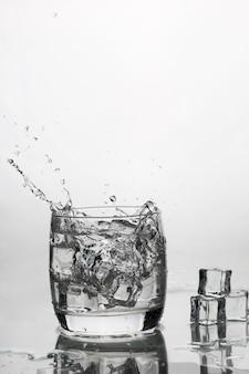 Eau avec de la glace dans un verre avec des éclaboussures