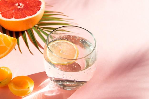 Eau avec de la glace et du citron boissons d'été fraîches aliments sains fruits et verre de soda sur fond de couleur rose