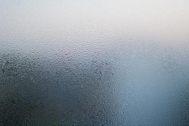 L'eau glacée tombe sur la fenêtre en verre