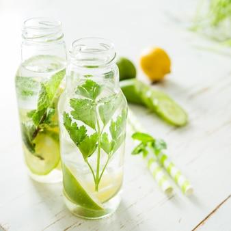 Eau infusée aux agrumes et aux herbes en bouteille de verre