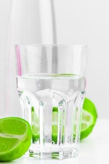 Eau infusée de désintoxication à la chaux dans une bouteille en verre sur fond blanc