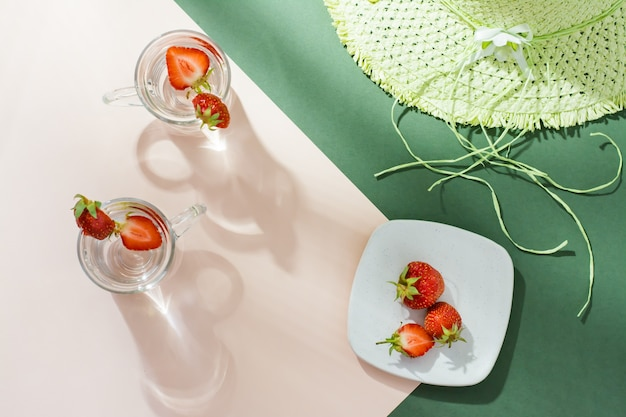 Eau infusée avec des fraises dans des verres, des baies sur une soucoupe et un chapeau de paille sur une table vert-rose dans une lumière crue avec des ombres.