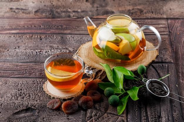 Eau infusée de fruits dans une théière avec des abricots séchés au thé, du bois, un récipient, des citrons verts vue grand angle sur une surface de carreaux de pierre