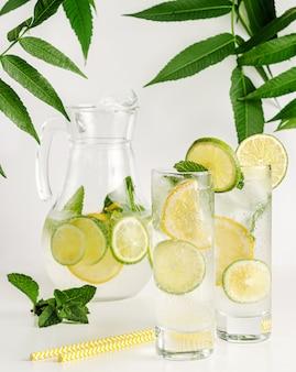 Eau infusée à la menthe, citron vert et citron sur blanc. boire sainement.