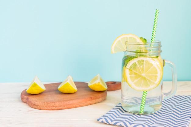 Eau de limonade aux agrumes avec tranches de citron et menthe, boisson saine et détoxifiante en été sur une table en bois avec fond bleu éclaircir