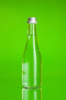 Eau limpide dans une bouteille sur fond vert