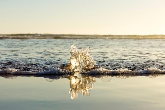 Eau de mer se brisant sur une sphère de verre sur la plage