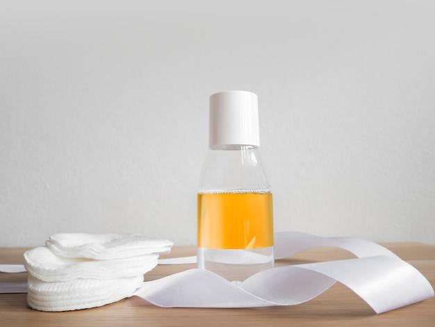 Eau micellaire diphasique avec tampons de coton sur une table en bois et un mur blanc.