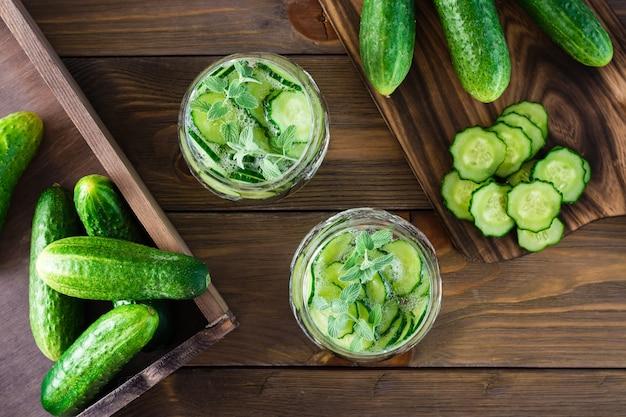 L'eau avec des morceaux de concombre, de glace et de feuilles de menthe dans un verre transparent et une planche à découper sur une table en bois. vue de dessus