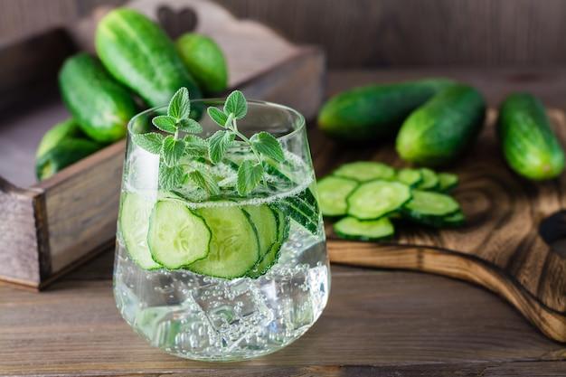 L'eau avec des morceaux de concombre, de glace et de feuilles de menthe dans un verre transparent et une planche à découper sur une table en bois