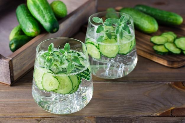 L'eau avec des morceaux de concombre, de glace et de feuilles de menthe dans des verres transparents sur table en bois
