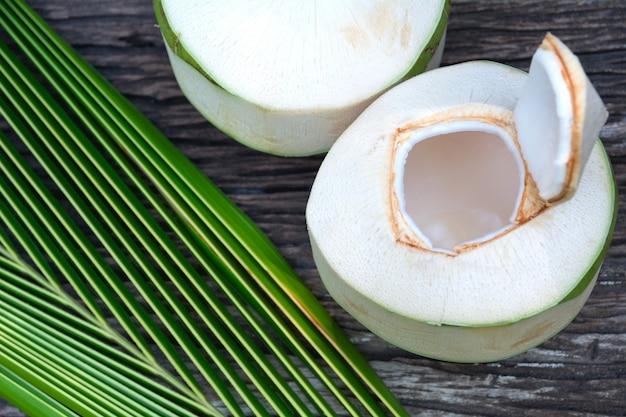 Eau de noix de coco organique fraîche avec des feuilles de noix de coco sur une table en bois.