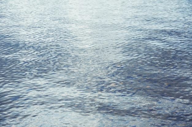 Eau ondulée bleue brillante le jour de pluie