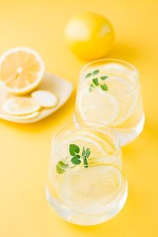 Eau pétillante au citron, mélisse et glace dans des verres et des tranches de citron sur une soucoupe sur une table jaune. boisson alcoolisée dure de seltz. vue verticale