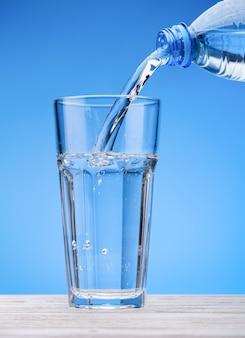 L'eau pétillante coule de la bouteille dans un grand verre. fond bleu, tableau blanc.