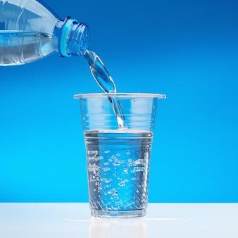 L'eau pétillante coule de la bouteille dans le verre.