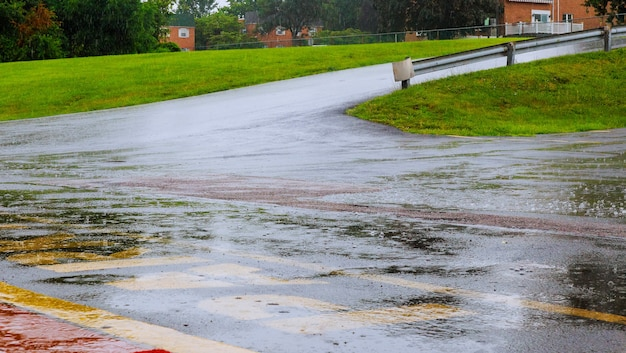 L'eau de pluie de la route tombe en arrière-plan avec la réflexion du ciel bleu et les cercles d'eau sur l'asphalte sombre. prévision de pluie.