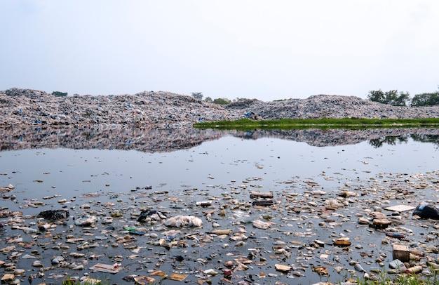 Eau polluée et grande montagne d'ordures