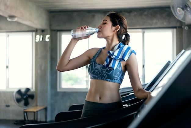 Eau potable assoiffée de femmes asiatiques après l'exercice dans la salle de fitness. mode de vie sain.