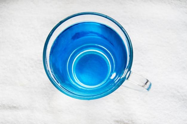 Eau potable avec des bulles dans un verre bleu clair