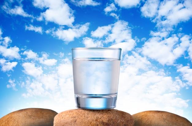 De l'eau potable fraîche et propre en verre sur des pierres