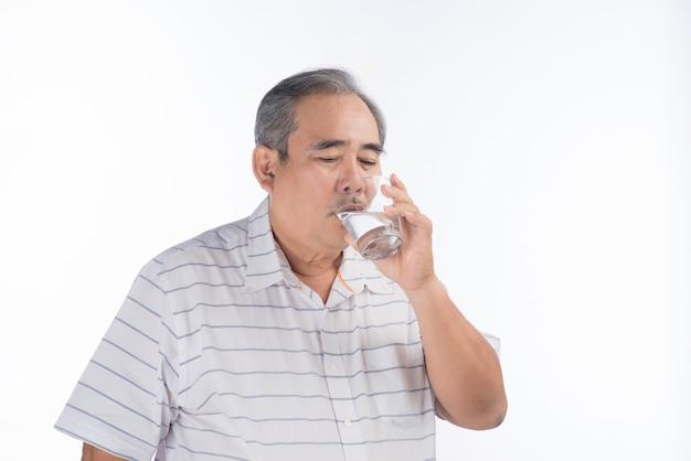 L'eau potable de l'homme senior asiatique. homme âgé tenant un verre transparent à la main.