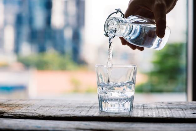De l'eau potable propre est versée d'une cruche dans une tasse en verre ronde sur une table en bois et une macro en gros plan de serviette vert clair sur un fond de nature verte à l'extérieur.