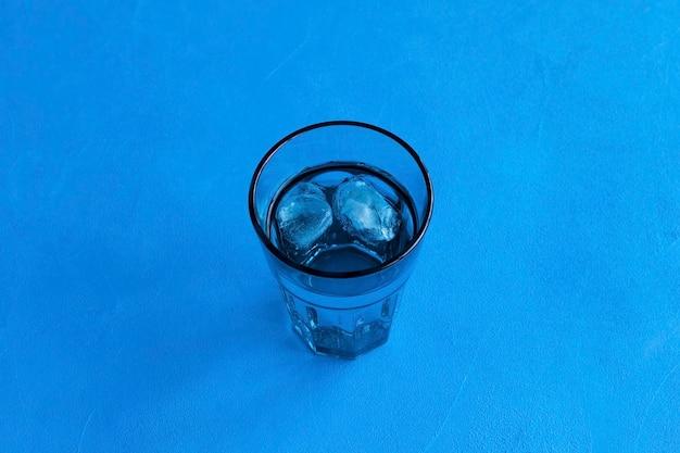 Eau potable pure avec de la glace dans un verre bleu transparent sur bleu