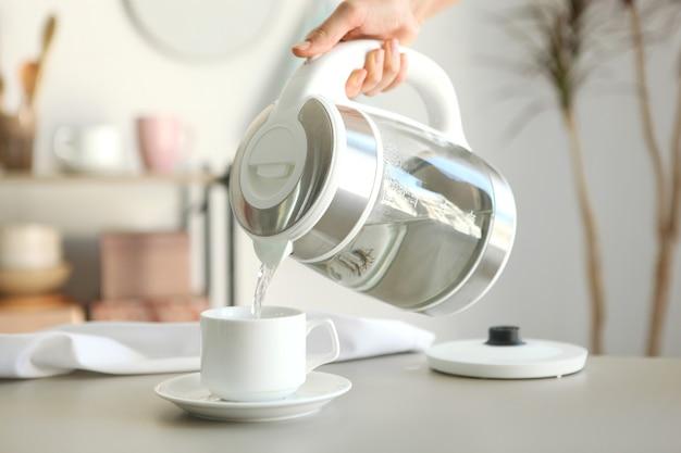 L'eau pure bout dans une bouilloire électrique sur la table de la cuisine
