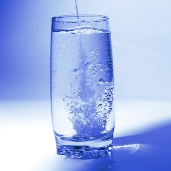 L'eau qui coule dans un verre transparent avec des bulles d'air