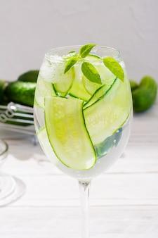 Eau rafraîchissante avec des tranches de concombre et de feuilles de basilic dans un verre et des concombres dans un panier