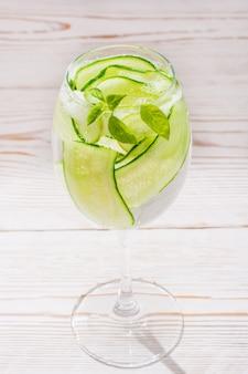 Eau rafraîchissante avec des tranches de concombre et de feuilles de basilic dans un verre sur une table en bois