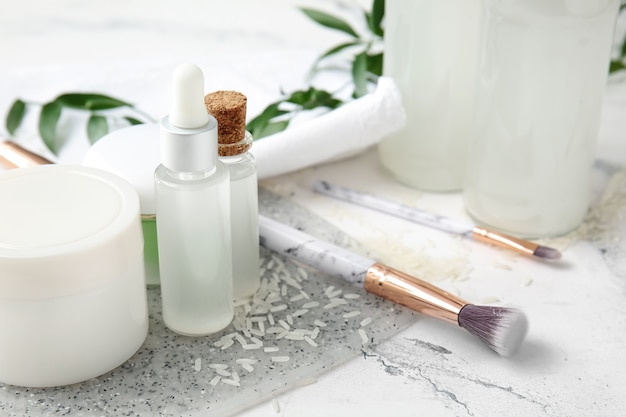 Eau de riz saine avec des fournitures cosmétiques sur une surface blanche