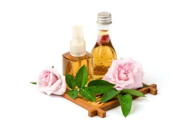 Eau de rose de damas et fleurs de rose de damas isolés sur blanc.