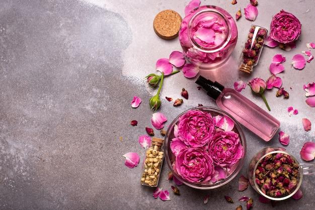 Eau de rose dans un bol en verre avec des pétales et des fleurs fraîches