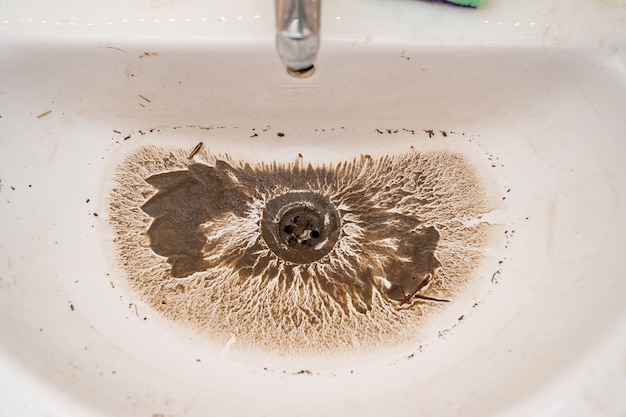 L'eau s'écoule dans le drain de l'évier sale une fois le blocage éliminé