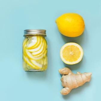 Eau saine de désintoxication au gingembre et citrucs dans un bocal sur fond bleu punch. bien-être.