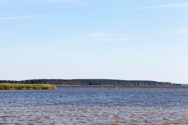 Eau sombre dans un grand lac, paysage d'été avec un ciel bleu