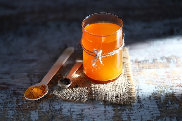 Eau tiède au curcuma dans un verre. curcuma et poivre noir. mise au point sélective. de l'eau dorée.