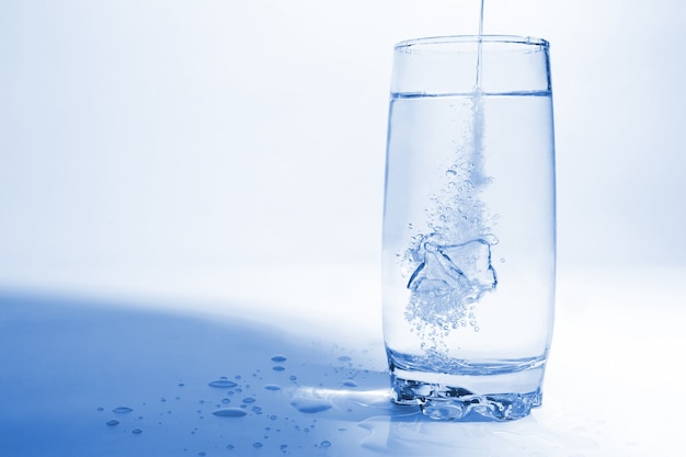 L'eau tombe en verre transparent avec des bulles d'air