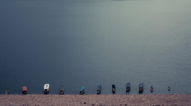 Eau turquoise encore surface avec des bateaux en bois typiques sur le lac