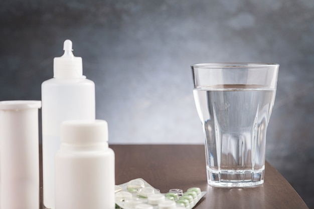 Eau en verre et médicament pour arvi ou grippe sur table