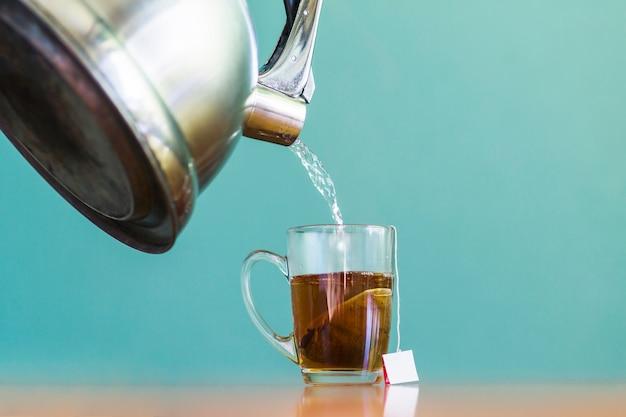 Eau versant dans la tasse de thé en verre