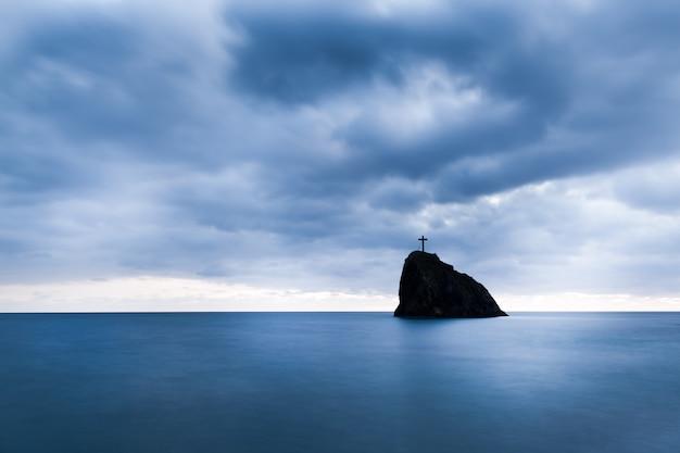 Eaux de mer encore, roches dures et croix sur le pic rocheux en soirée le jour d'été avec ciel sombre à l'arrière-plan
