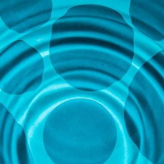 Les eaux ondulées dans une piscine avec des taches bleues plus foncées à plat