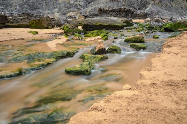 Des eaux traversant le sable et des pierres avec de la mousse